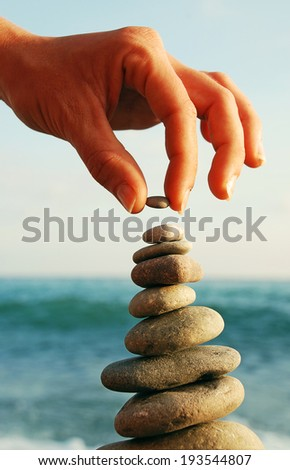 Balanced Stones. Stack of volcanic pebbles on seashore - stock photo