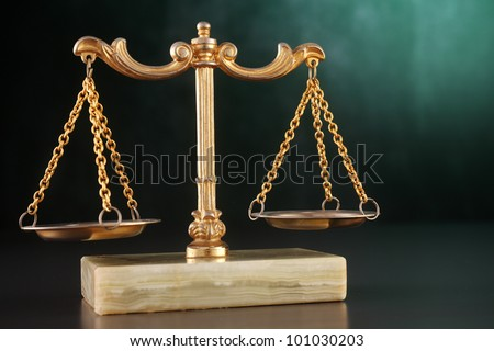 Balanced weight scale against green background - stock photo