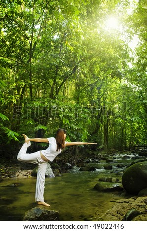 Balancing. Female practises balancing at  nature tropical forest in a morning. - stock photo