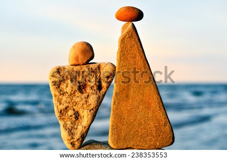 Balancing of two triangle stones on the seacoast - stock photo
