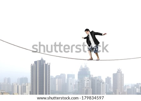 Balancing on rope with city view background - stock photo
