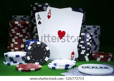 Balancing pair of aces playing cards surrounded by poker chips on casino green felt. Gambling concept - stock photo