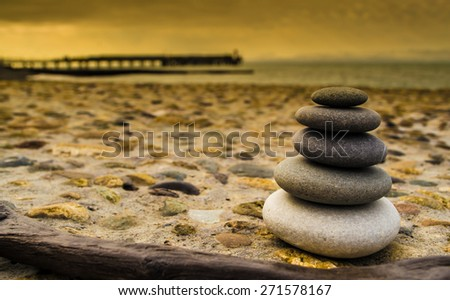 Balancing stones on a rough stone background with the sea and a pier in the distance - stock photo