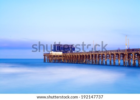 Balboa pier in Newport Beach, California during sunrise shows the wood structure of the pier and a vibrant, blue sky and seascape.  Image shot in slow motion to capture the unique water texture. - stock photo