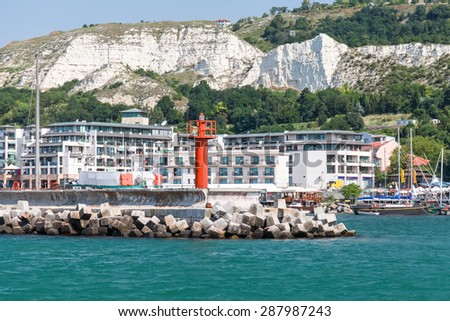 Balchik resort town. Entrance to port, red lighthouse on the pier. Coast of the Black Sea, Varna region, Bulgaria - stock photo