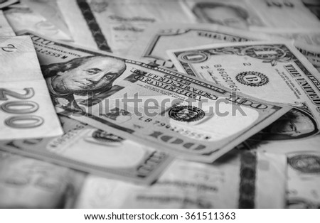 Balck and white photo of a collection of foreign currencies from countries spanning the globe. Many currencies as background concept global money. Soft selective focus and shallow depth of field - stock photo
