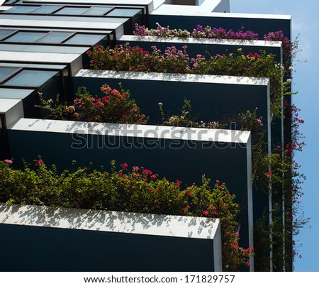 Balconies of flowers in apartment building. - stock photo