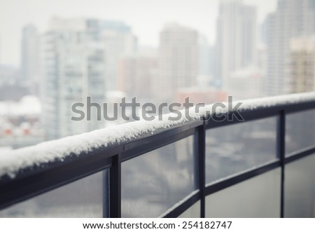 Balcony black railing with glass, winter snow, blurry city town background with copy space for text, toned with filter, selective focus, shallow depth of field - stock photo