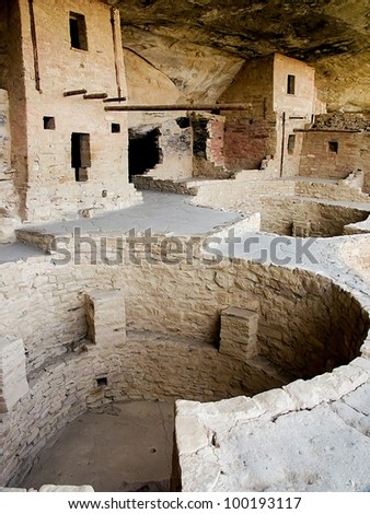 Balcony House ruin at Mesa Verde National Park in the Four Corners area of Colorado showing structures and a round kiva in the foreground. - stock photo
