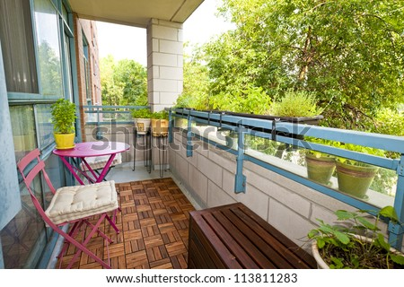 Balcony of condo with patio furniture and plants - stock photo