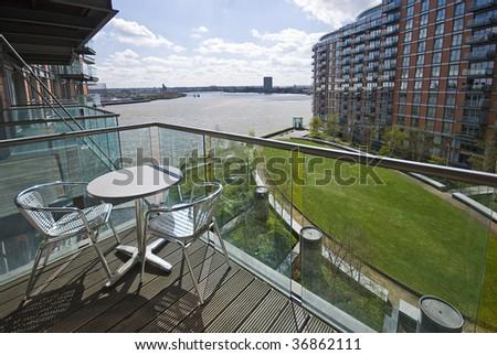 balcony on riverside with aluminum garden furniture - stock photo