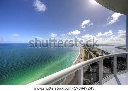 Balcony with seating arrangement, white marble floor and paradise ocean view. - stock photo