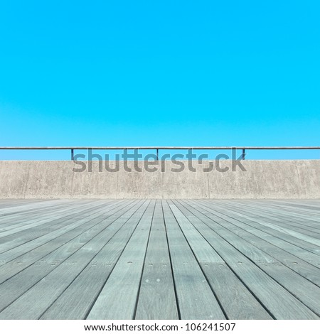 Balcony, Wooden plank floor, concrete fence and blue sky. Outdoor architecture, bottom perspective - stock photo