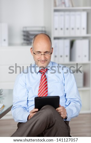 Bald businessman browsing the internet through tablet computer - stock photo