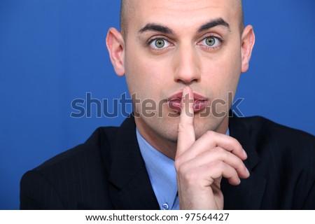 Bald businessman making shush gesture - stock photo