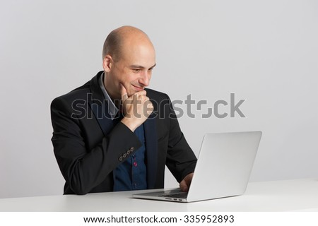 bald businessman sits at the desk with laptop - stock photo