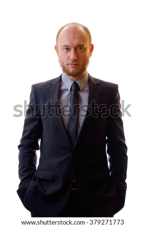Bald businessman with a beard wearing a black suit, shirt and tie looks like running his company. Portrait of a standing person. Hands in pockets. - stock photo