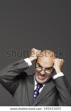 Bald businessman with fists pounding bald head against gray background - stock photo