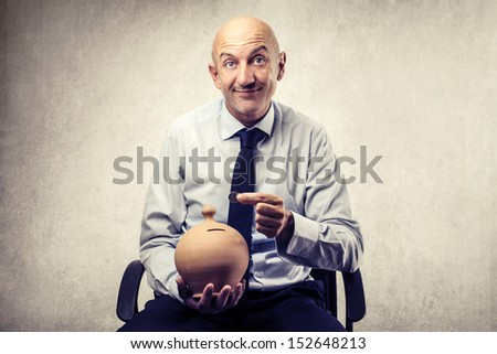 bald businessman with piggy bank and coin - stock photo