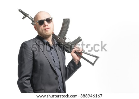 Bald man in a gray suit and sunglasses holding a machine gun on his shoulder. Isolated - stock photo