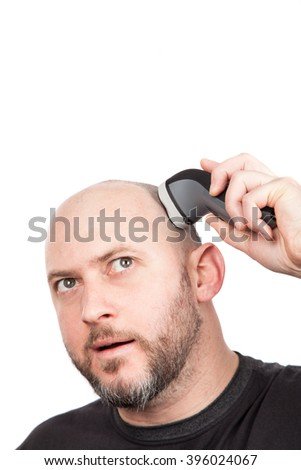 Bald man with beard shaving his head with an electric shaver - stock photo
