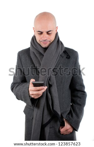 Bald man with tweed coat and scarf using his smart phone smiling. Isolated - stock photo