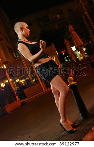 Bald prostitute in the street at the evening - stock photo