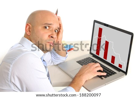 bald worried business man in stress watching sales and finance collapse graphic on computer monitor - stock photo