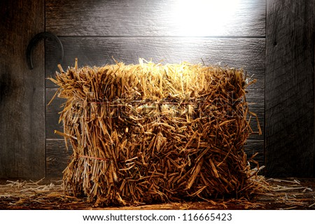 Bale of straw hay on wood aged floor in an antique and dusty old wooden barn - stock photo