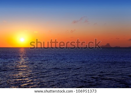Balearic sunset from La Savina in Formentera with Es Vedra of Ibiza in background - stock photo