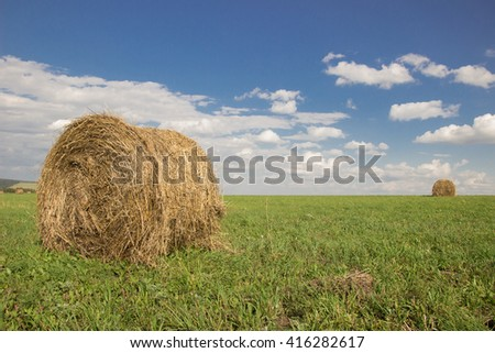 Bales of hay gold on green grass and blue sky with clouds - stock photo