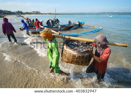Bali Indonesia - Apr 5, 2016 : Fishermen carry their catch to the shore at Jimbaran village, Bali on Apr 5, 2016 in Bali. Jimbaran village is among famous place to see fisherman life in Bali. - stock photo