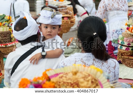 Bali Indonesia Apr 4, 2016 : Young Balinese with his family attending Meprani Ceremony at a tample in Batur. Meprani ceremony is one of Hindus ritual as a ceremony that is held once a year. - stock photo