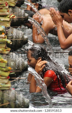 BALI, INDONESIA - JULY 15: Balinese Hindu families come to the sacred springs of Tirta Empul in Bali, Indonesia to pray and cleanse their soul on July 15, 2012. - stock photo
