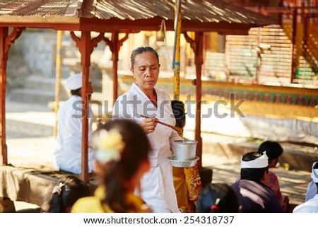 BALI, INDONESIA JULY 12, 2014: Balinese woman given blessing to people in the temple after the religious ceremony - stock photo