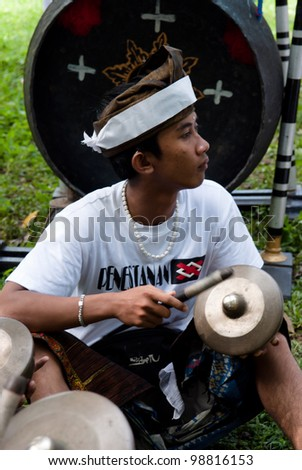 BALI, INDONESIA-JULY 14: unidentified Balinese musician plays a traditional musical instrument  during the cremation ceremony in Penestanan, Bali on July 14, 2010. - stock photo