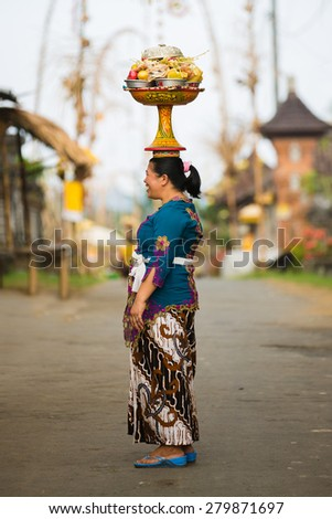BALI, INDONESIA - JUNE 2: Balinese woman loads the offering of food in wooden jar on her head for the ceremony in Ubud temple, Bali on June 2, 2014 - stock photo