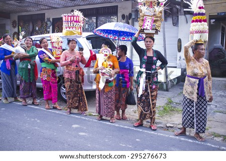 BALI, INDONESIA- JUNE 21, 2015: Part of cremation ceremony. Balinese women in traditional clothes and with donations standing along the road. Village procession - stock photo