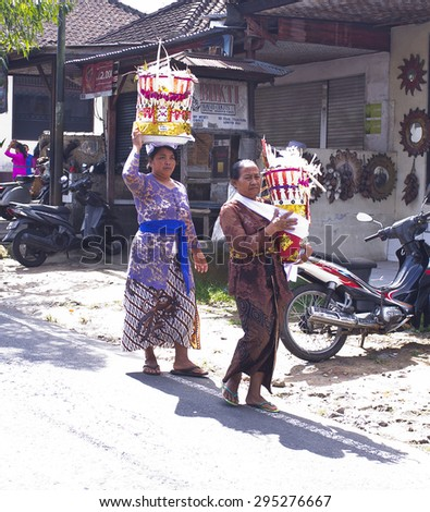 BALI, INDONESIA- JUNE 21, 2015: Part of traditional Balinese cremation ceremony. Two Balinese women in traditional clothes and with donations walking along the road.  - stock photo