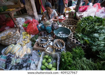 BALI, INDONESIA - MARCH 16, 2016: Commercial activities in the main Ubud market in the morning, showing trader selling vegetables. Agricultural produce comes direct from the farmers here in Bali. - stock photo
