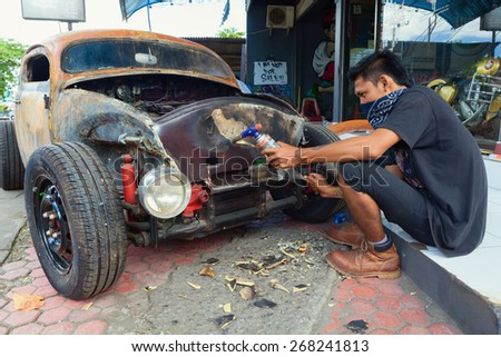 BALI, INDONESIA - MARCH 20: Young Balinese man cleans a body of old volkswagen beetle during the making and vintage custom hotrod car in the auto and moto repair shop in Bali island on 20 March, 2015 - stock photo