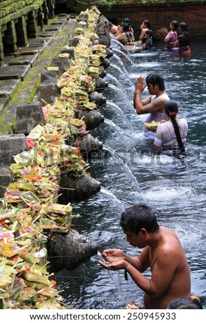 BALI, INDONESIA - MAY 1: Balinese Hindu families come to the sacred springs of Tirta Empul in Bali, Indonesia to pray and cleanse their soul on May 1,2011. - stock photo