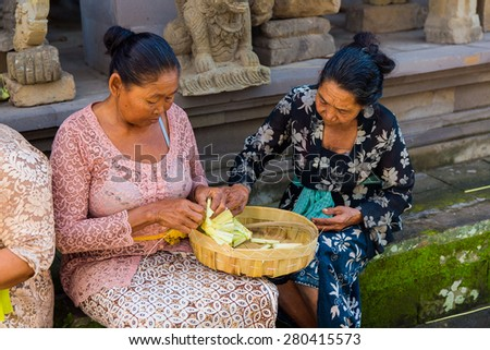 Bali, Indonesia, May 3, 2015. Balinese women make decorations of palm leaves for the feast at the local temple in Bali, Indonesia. Offering flowers and other gifts is very popular tradition on Bali. - stock photo