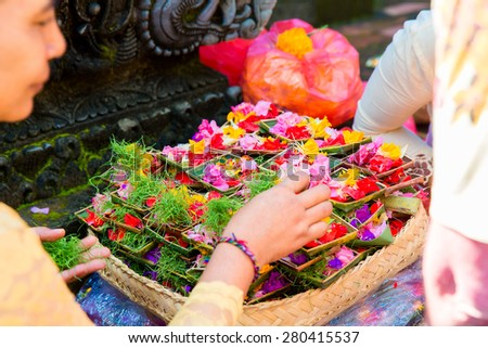 Bali, Indonesia, May 3, 2015. Female hands offering food to God, traditional Balinese offerings to gods in Bali with flowers and aromatic sticks - stock photo