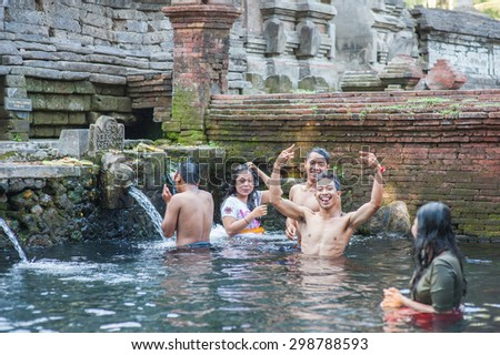 BALI, INDONESIA - NOVEMBER 3RD 2014 : Balinese people having fun after their cleansing in the Holy Spring at Tirtha Empul Bali, Indonesia. - stock photo