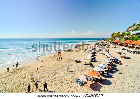 BALI, INDONESIA - OCT 18: Wide sand beach with tourists, umbrellas and beds  on October 18, 2010. Dreamland beach, Bali, Indonesia. The Dreamland is one of the most popular surfing areas of Bali. - stock photo