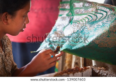 BALI, INDONESIA - Sep 21: Balinese woman applies wax on a piece of batik, on Sep 21, 2012 in Bali, Indonesia. Batik-making is an important part of Indonesian culture. - stock photo