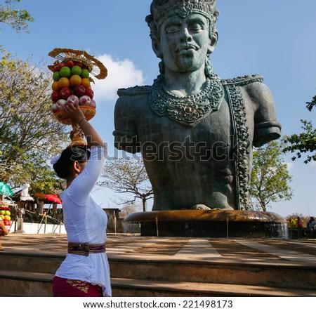 BALI, INDONESIA - SEPTEMBER 19, 2014: A devotee carries a fruit basket as offerings to Lord Vishnu at the Garuda Wisnu Kencana at Uluwatu, Bali Island. - stock photo