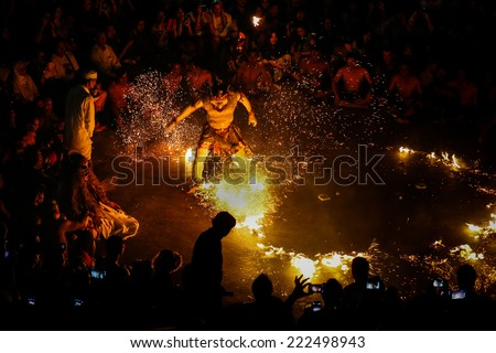 BALI, INDONESIA - SEPTEMBER 19, 2014: Hanuman puts out the fire during a performance of the traditional Balinese Kecak Fire Dance at the Uluwatu Temple in Bali.  - stock photo