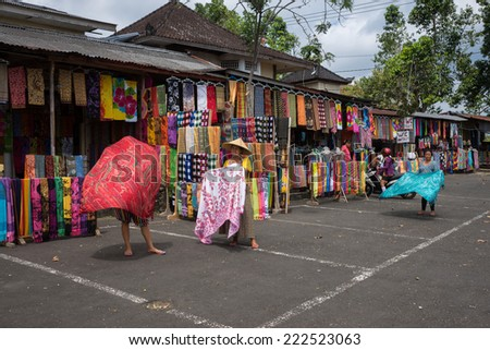 BALI, INDONESIA - SEPTEMBER 20, 2014: Vendors display sarong wraps for sale or rental to tourist visiting the Besakih Temple Complex. - stock photo